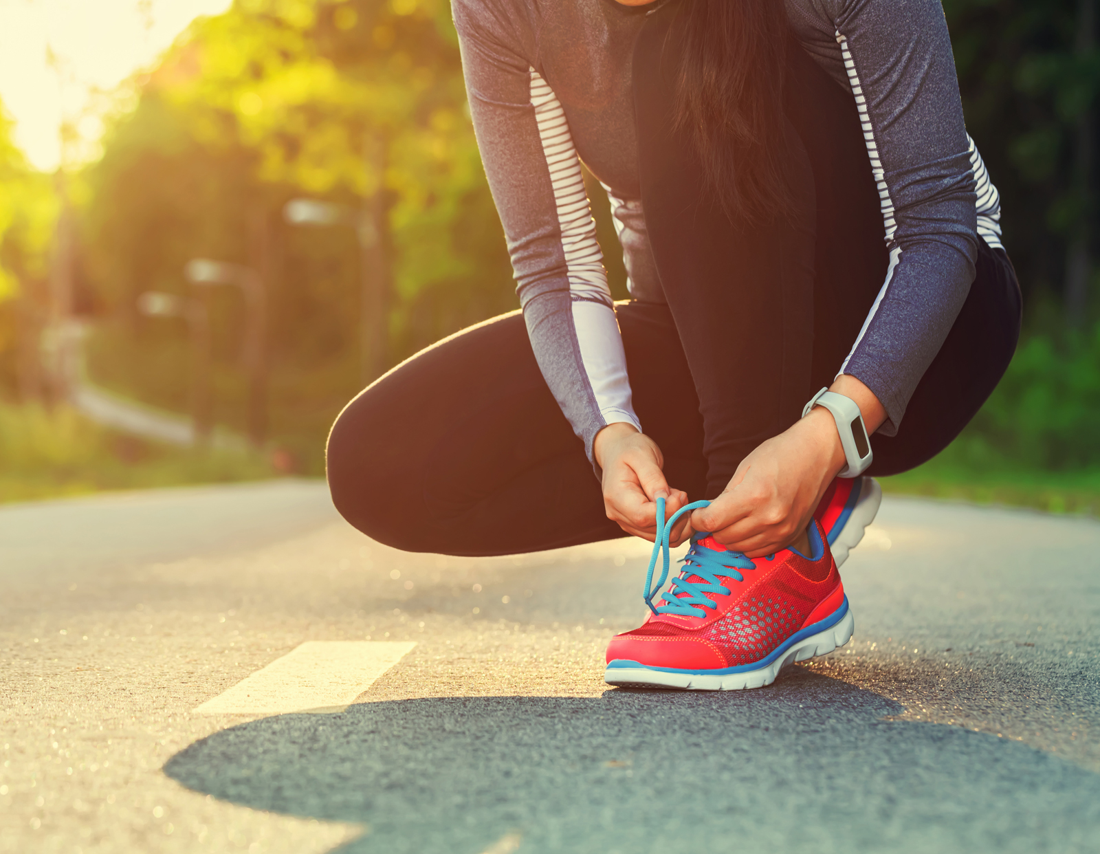 Female runner tying her shoes preparing for a jog